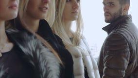 Ein junger bärtiger Mann betrachtet drei Frauen herein stock video