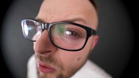 Ein junger, bärtiger Mann mit den Gläsern, die im Guckloch schauen stock footage