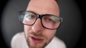 Ein junger, bärtiger Mann mit den Gläsern, die im Guckloch schauen Misstrauen sucht nach etwas stock video footage