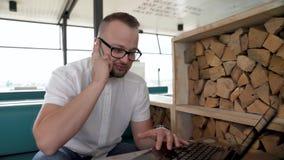 Ein junger, bärtiger Mann mit Gläsern arbeitet an seinem Notizbuch auf der Terrasse und empfängt einen Telefonanruf stock footage