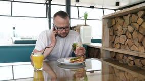 Ein junger, bärtiger Mann mit Gläsern Sandwich essend und Orangensaft trinkend Mann empfängt einen Telefonanruf am lucnh stock footage