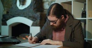 Ein junger bärtiger Mann unterzeichnet Papiere nahe dem Kamin stock footage