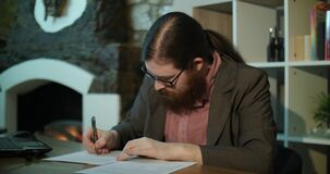 Ein junger bärtiger Mann unterzeichnet Papiere nahe dem Kamin stock video