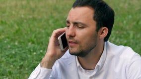Ein junger Büroangestellter spricht am Handy am Stadtpark stock video footage