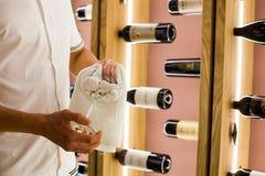 Ein junger Barmixer wischt Tuchweingläser bei der Arbeit im Restaurant auf dem Hintergrund von Flaschen Wein ab Stockbilder
