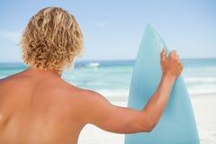 Ein junger blonder Mann, der ein gehocktes Surfbrett anhält Lizenzfreie Stockfotografie