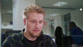 Ein junger blonder Mann, der in einem Büro arbeitet Stockfotos