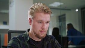 Ein junger blonder Mann, der in einem Büro arbeitet Lizenzfreies Stockbild