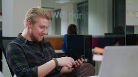 Ein junger blonder Mann, der ein Telefon im Büro verwendet Stockfotografie