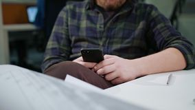 Ein junger blonder Mann, der ein Telefon im Büro verwendet Stockbilder