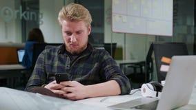 Ein junger blonder Mann, der ein Telefon im Büro verwendet Lizenzfreies Stockfoto