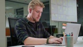 Ein junger blonder Mann, der zuhause an dem Laptop arbeitet Stockbilder