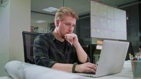 Ein junger blonder Mann, der zuhause an dem Laptop arbeitet Lizenzfreies Stockfoto