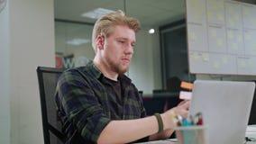 Ein junger blonder Mann, der zuhause an dem Laptop arbeitet Stockfotografie