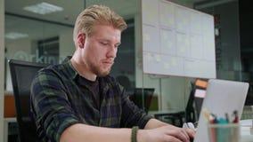 Ein junger blonder Mann, der zuhause an dem Laptop arbeitet Stockbild