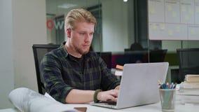 Ein junger blonder Mann, der zuhause an dem Laptop arbeitet Lizenzfreie Stockbilder