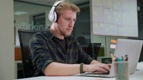 Ein junger blonder Mann, der zuhause an dem Laptop arbeitet Lizenzfreie Stockfotos