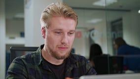 Ein junger blonder Mann, der zuhause den Laptop betrachtet Lizenzfreies Stockfoto