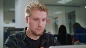 Ein junger blonder Mann, der zuhause den Laptop betrachtet Stockbild