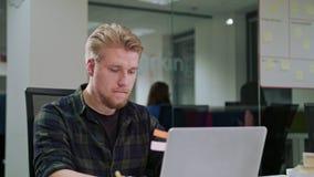 Ein junger blonder Mann, der zuhause den Laptop betrachtet Lizenzfreie Stockbilder