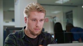 Ein junger blonder Mann, der zuhause den Laptop betrachtet Lizenzfreies Stockbild