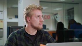 Ein junger blonder Mann, der zuhause den Laptop betrachtet Stockfotos