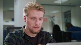 Ein junger blonder Mann, der zuhause den Laptop betrachtet Stockbilder
