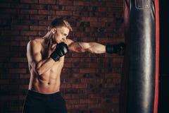 Ein junger Boxer in den schwarzen Handschuhen mit einem nackten Torso arbeiten Streiks auf Sandsack aus Lizenzfreies Stockbild