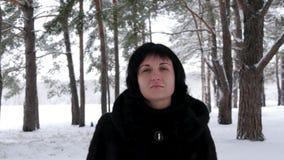 Ein junger Brunette in einem Pelzmantel geht durch einen schneebedeckten Wald oder einen Park an einem eisigen Tag und an den Bli stock footage