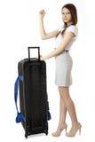 Ein junger, dünner Mädchenjugendlicher 16 Jahre alt, steht nahe bei einem enormen, schwarzen Koffer auf Rädern. Jugendlich per Anh Stockbild