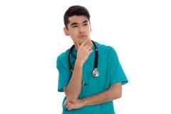 Ein junger Doktor mit Stethoskop blickt in Richtung Stockfotografie