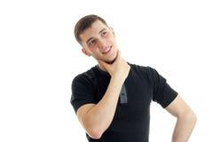 Ein junger durchdachter Kerl in einem schwarzen T-Shirt und im Schauen oben lächelnd stockfotografie