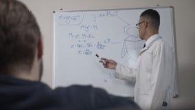 Ein junger erfolgreicher afrikanischer Wissenschaftler in einem weißen Mantel und in den Gläsern, Stände an der Tafel mit Formeln stock video
