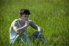 Ein junger erwachsener Mann, der draußen an einem Sommer ` s Tag sitzt Stockfotos