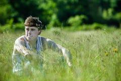 Ein junger erwachsener Mann, der draußen an einem Sommer ` s Tag sitzt Lizenzfreie Stockfotos