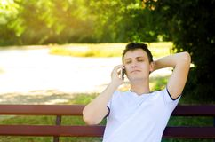 Ein junger europäischer Kerl sitzt auf einer Bank im Park und spricht am Telefon, wirft seinen Arm hinter seinen Kopf und schließ stockfotos