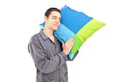 Ein junger fauler Kerl, der ein Kissen und ein Schlafen hält Stockbilder