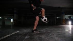 Ein junger Fußballmann, der seine Fußballfähigkeiten mit dem Ball ausbildet stock footage