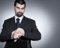 Ein junger Geschäftsmann überprüft die Zeit Lizenzfreie Stockfotos