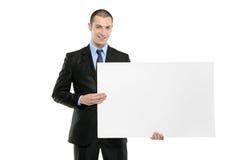 Ein junger Geschäftsmann, der eine weiße unbelegte Karte anhält Lizenzfreie Stockfotos