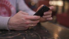 Ein junger Geschäftsmann, der an einem Tisch in einem Café unter Verwendung des iphone sitzt und eine Mitteilung schreibend - erf stock video
