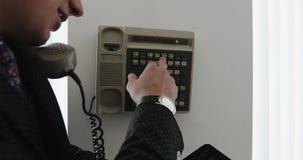 Ein junger Geschäftsmann in einer Klage benutzt ein Weinlesetelefon für interne Kommunikation im Büro stock video