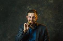 Ein junger Geschäftsmann hält eine Münze von bitcoite in seiner Hand lizenzfreie stockfotos