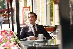Ein junger Geschäftsmann kam, in einem Café zu Mittag zu essen, sitzt er an einem Tisch und wartet jemand lizenzfreies stockbild