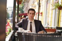 Ein junger Geschäftsmann kam, in einem Café zu Mittag zu essen, sitzt er an einem Tisch und wartet jemand stockbild