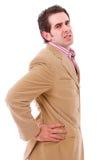 Ein junger Geschäftsmann mit Rückenschmerzen Stockfotos