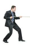 Ein junger Geschäftsmann, der ein Seil zieht Stockbild