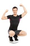Ein junger glücklicher Athlet auf einer Gewichtskala Lizenzfreie Stockfotografie