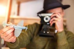 Ein junger glücklicher Mann in einem Hut hält ein Flugzeug und die Karte bereitet sich für die Reise in einer Wohnung, eine Kamer lizenzfreie stockbilder