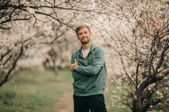 Ein junger glücklicher Mann steht unter dem blühenden Garten lizenzfreies stockbild